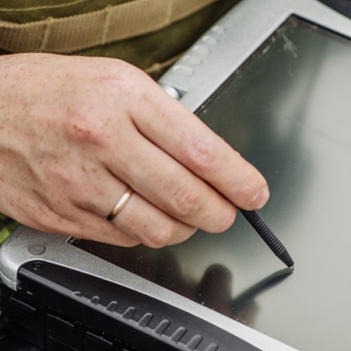 Military person writing on a ipad
