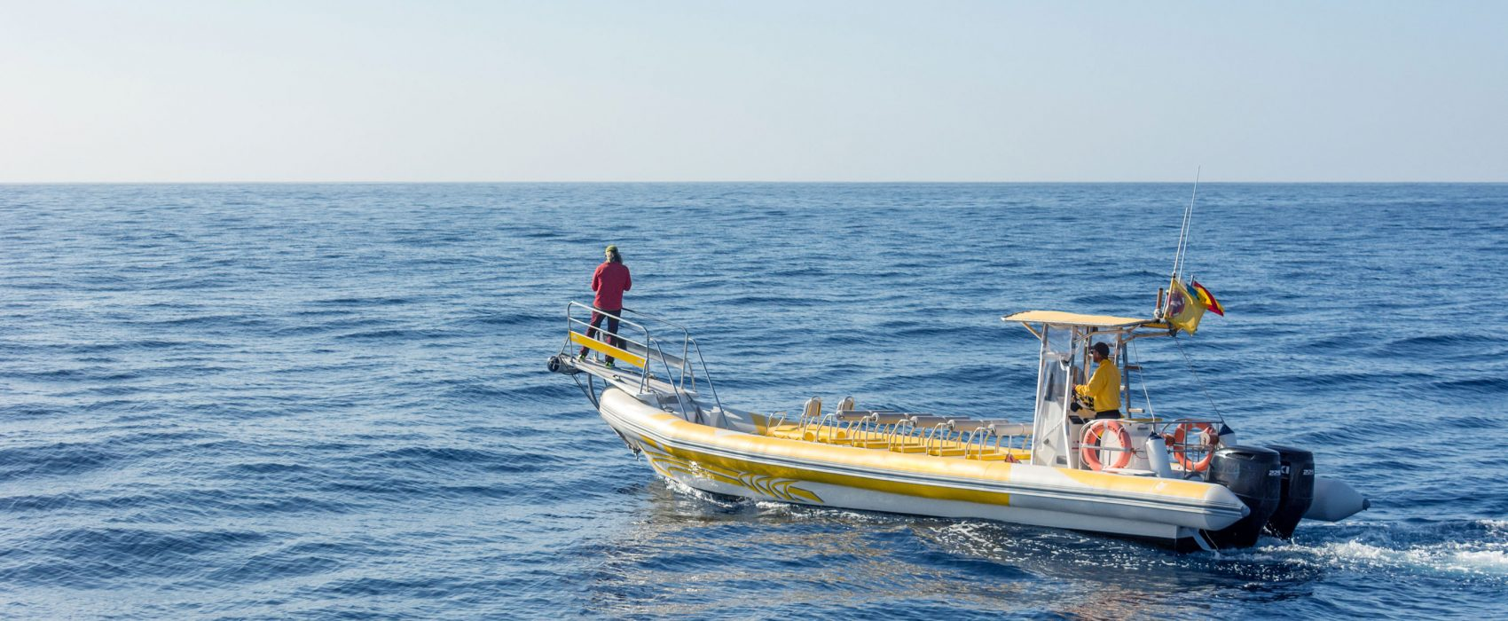 Yellow and White Boat alone in the Ocean with two fishermen